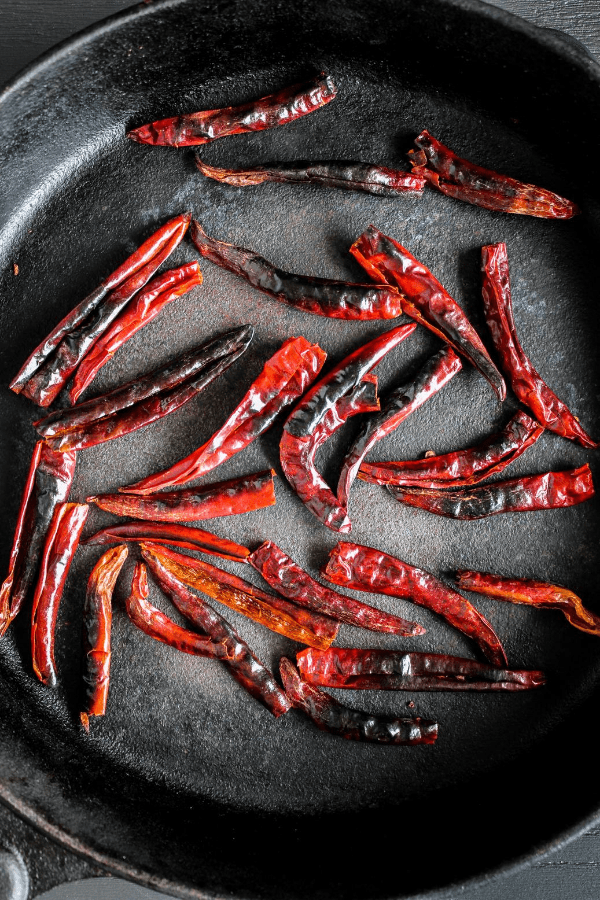 Top down shot of toasted chiles in a skillet.