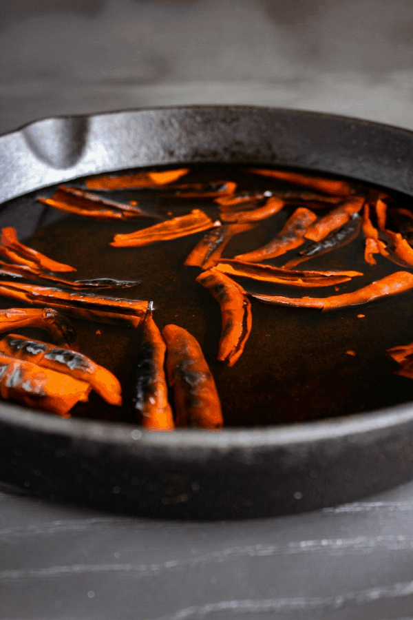Chile de árbol soaking in water in a cast iron skillet.