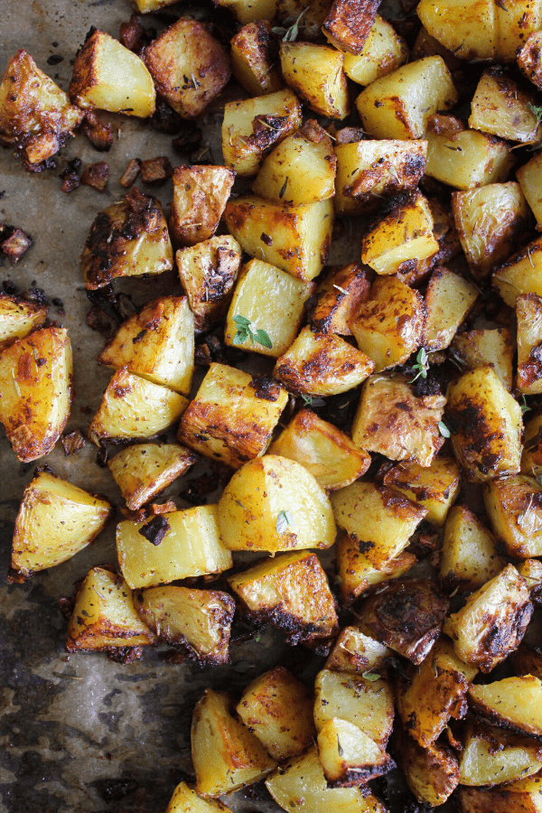 Roasted French onion potatoes on a baking sheet sprinkled with fresh thyme shot from above.