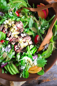 Walnut bowl filled with grilled steak salad dressed in habanero peach dressing shot from above.