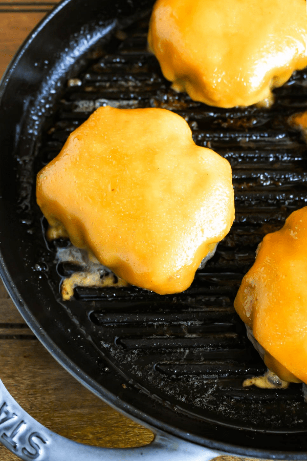 Top down shot of hatch chile burgers with melted cheese in a cast-iron griddle.