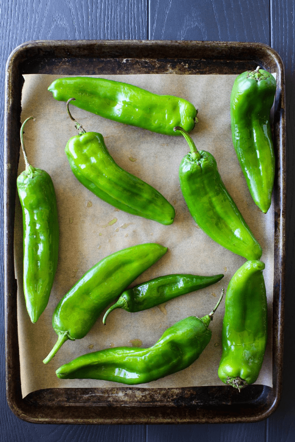 Top down shot of uncooked hatch chiles on a baking sheet lined with parchment paper.