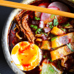 Close-up of bowl of birria ramen with quesadilla strips with a single chopstick laid across it.