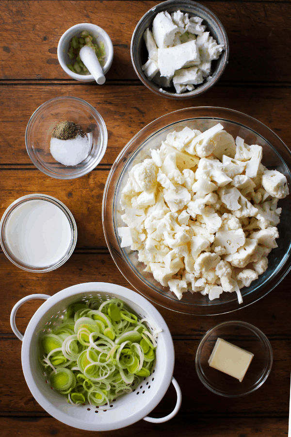 Top down shot of ingredients for goat cheese mashed cauliflower with sautéed leeks on a wood surface.