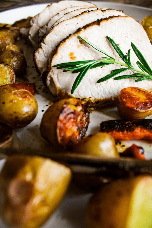 Close up shot of slice pork roast with roasted veggies.