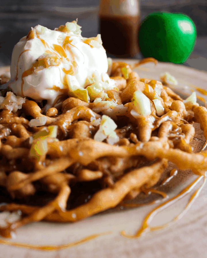Funnel cake topped with apples, caramel, and vanilla ice cream with a green apple and bottle of caramel in background.