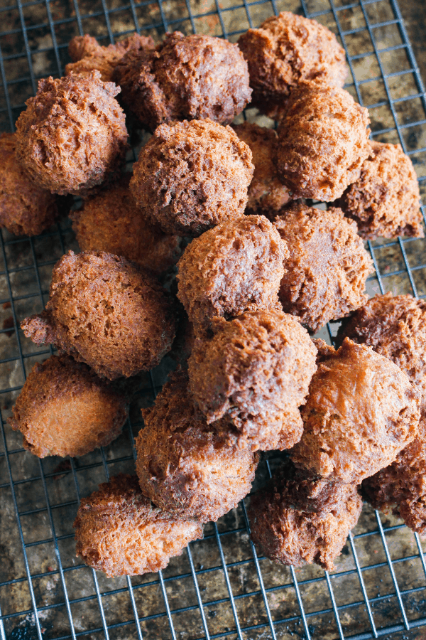 Stack of fried donut holes on a wire cooling rack.