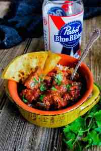 A bowl of spicy pork chili with quesadillas and a PBR glass.