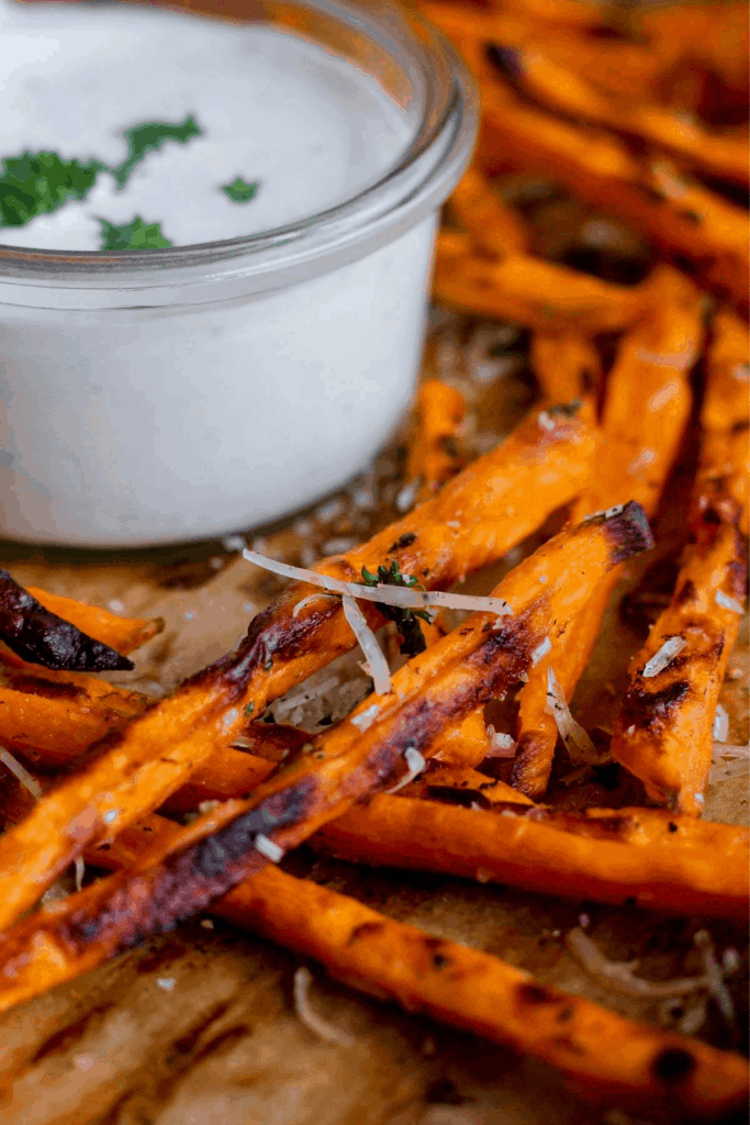 Baked truffle fries on a tray with small bowl of ranch.