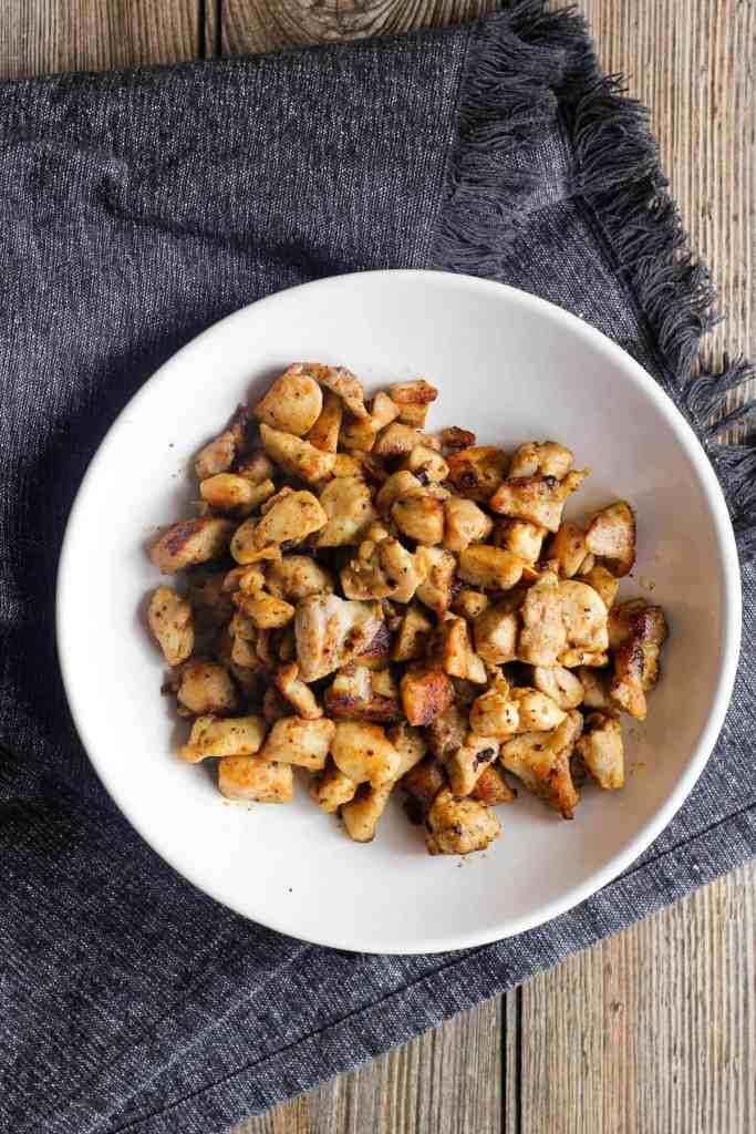 Sautéed chicken pieces in a white bowl.