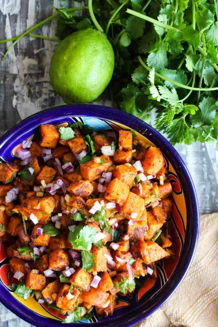 Bowl of Mexican potato salad with cilantro and a lime.