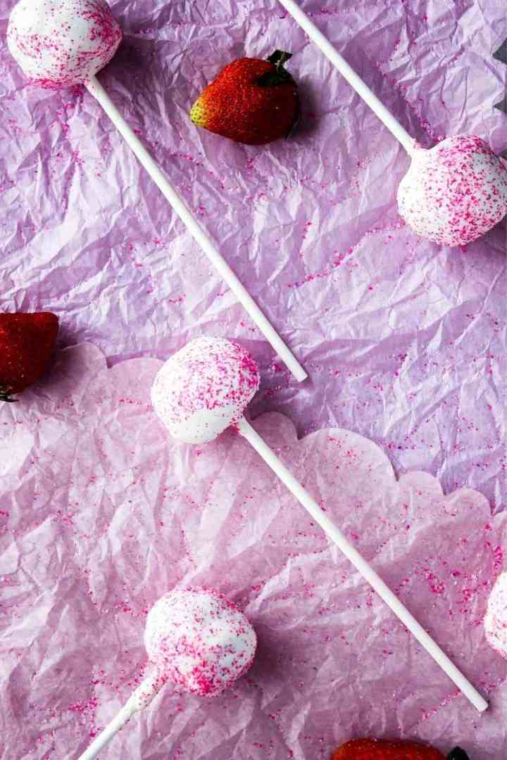 Scattered cake pops and strawberries on pink surface.
