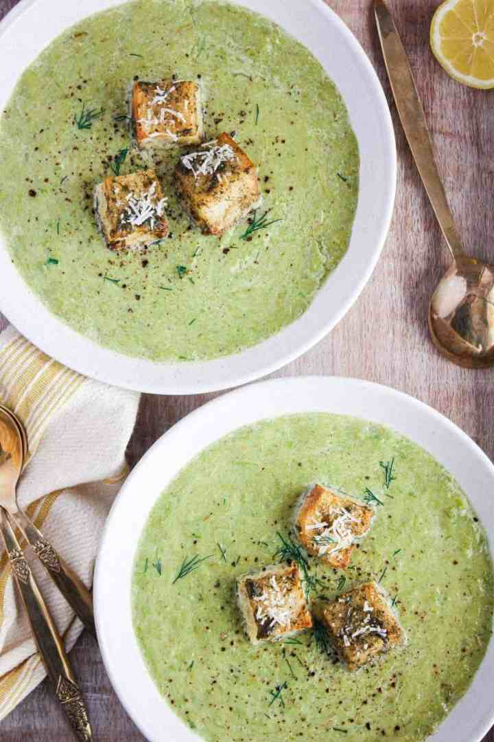 Close up of two bowls of asparagus leek soup.