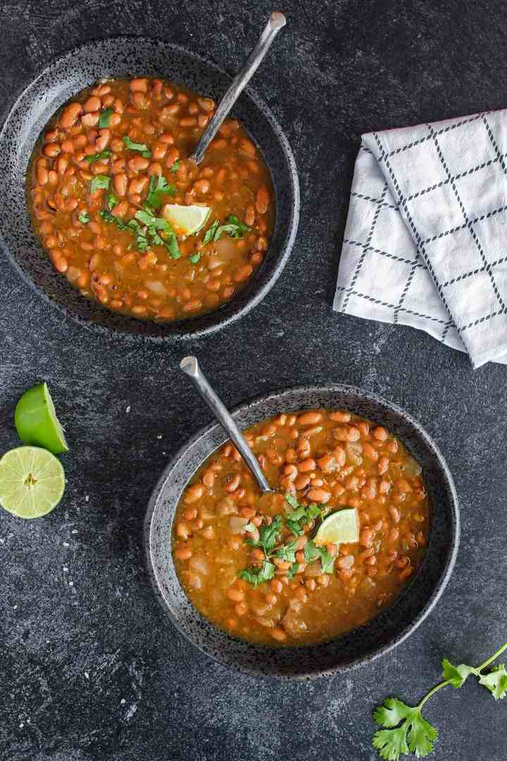 Two bowls of salsa verde pinto beans with lime halves and a towel.