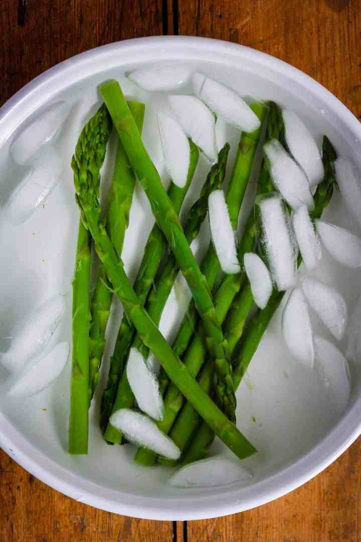 Blanched asparagus in ice water bath.