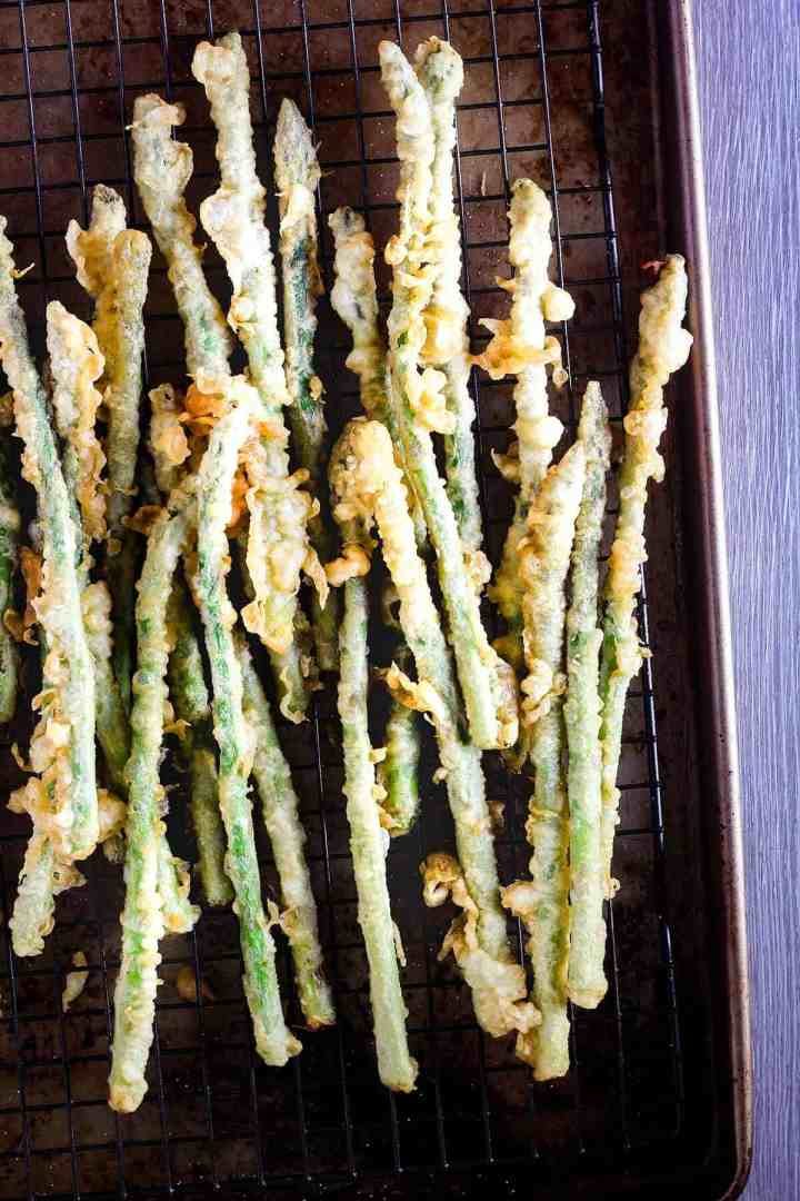 Asparagus tempura on sheet pan.