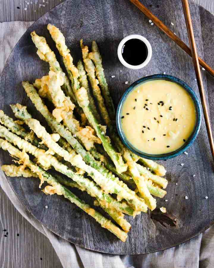 Asparagus tempura on a tray with bowl of miso aioli, soy sauce, and chop sticks.