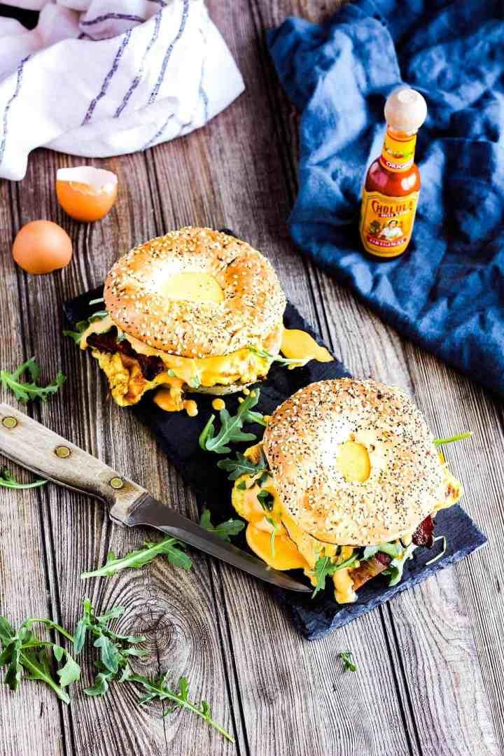 Two bagel breakfast sandwiches on a platter.