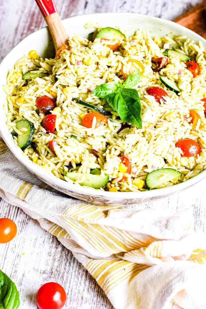 Large bowl of orzo pesto pasta salad with vegetables and a towel.
