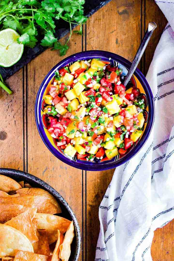 Bowl of pineapple pico and a bowl of chips with a lime and cilantro.