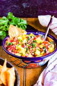 A bowl of pico, a bowl of chips, and a bunch of cilantro.