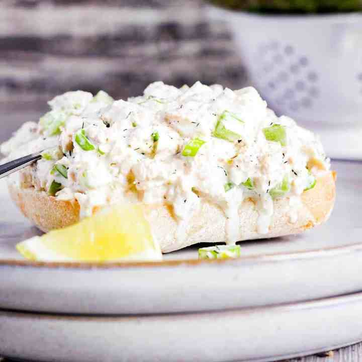 A slice of bread topped with dill tuna salad with lemon.