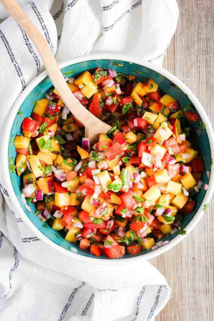 Mixed peach salsa in a bowl with a spoon.