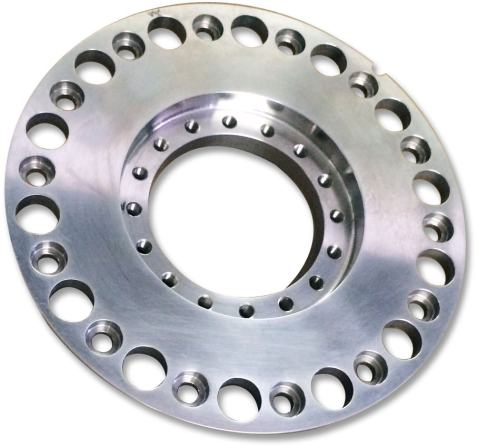 photo of precision metal disc with many mounting holes around outer and inner edges created by Tape Turn Specialties, Inc. of El Monte, California