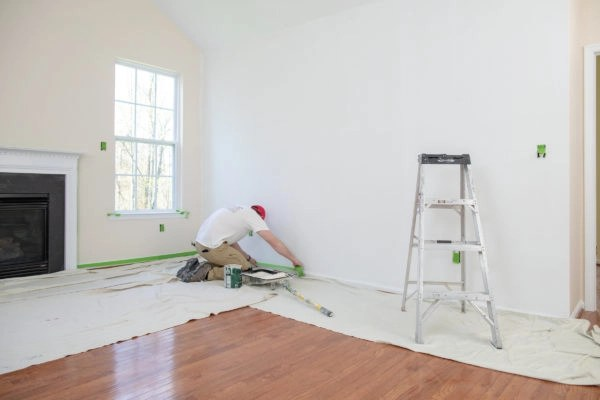 Applying tape to baseboards of home.