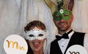A couple using a photobooth at their wedding reception