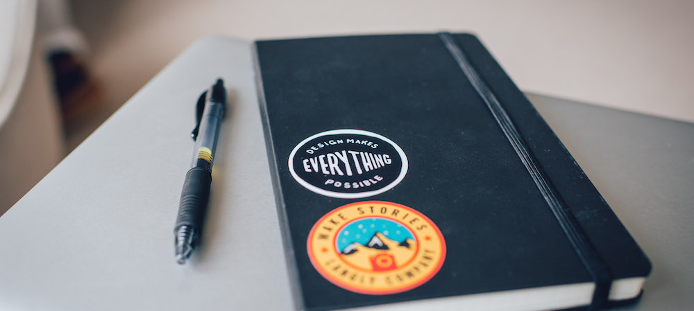 why designers should care about journaling. Image credit: https://www.pexels.com/photo/black-and-white-organizer-beside-red-click-pen-38167/