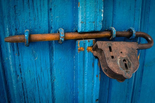 blue wooden door with a big rusted old fashioned lock