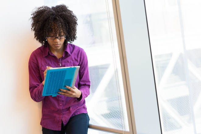 Black woman with natural hair looks down at her tablet