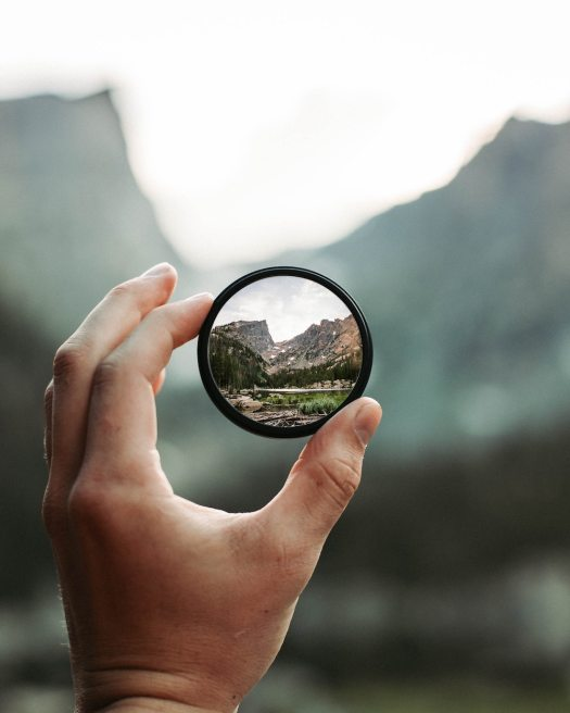 a white hand holds up a small round mirror that shows the clear refleciton of the mountains, the background is blurred