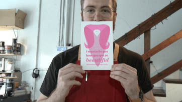 Ryan Tempro, 26, holding up his printed card creation in his letterpress shop in St. Augustine, Florida on Monday, February 13, 2017. Tempro has his own well-kept mustache, therefore his signature personal cards always involve mustaches.