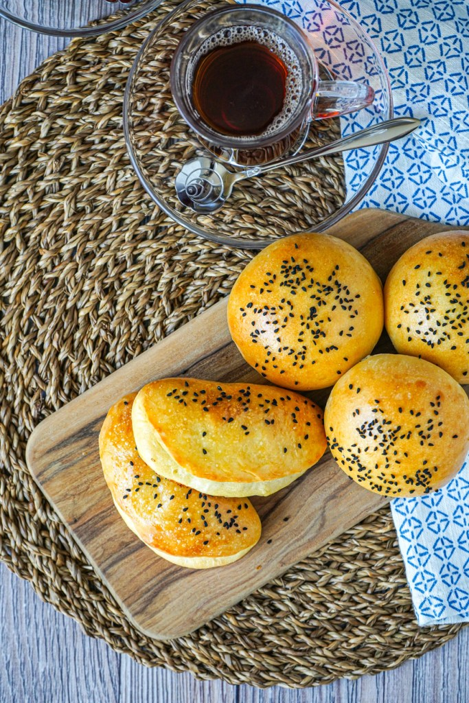 Aerial view of five Peynirli Poğaça (Turkish Cheese Buns) on a wooden board next to a glass of tea.