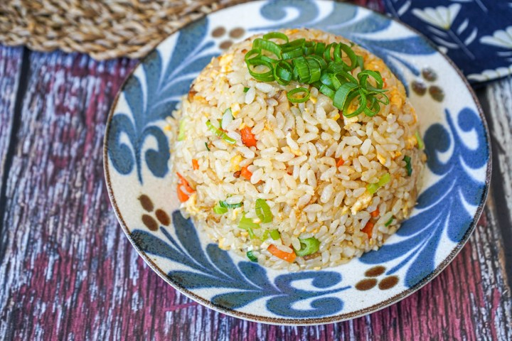 Close up of Chahan (Japanese Fried Rice) on a plate and topped with sliced green onions.