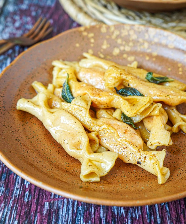Sweet Potato Caramelle on a brown plate with crispy sage.