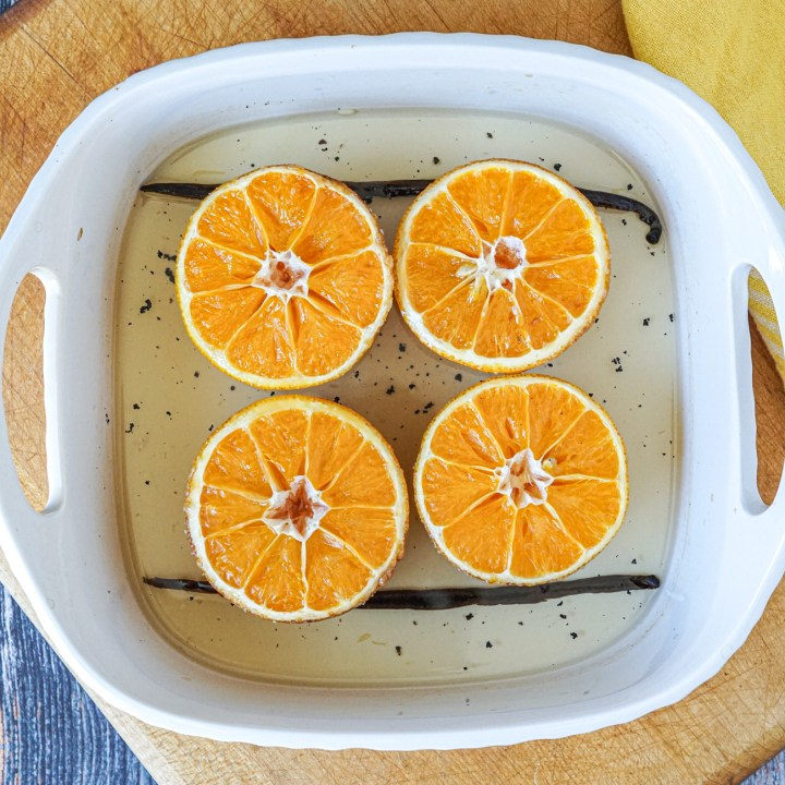 Roasted oranges in a square white baking pan with vanilla syrup.