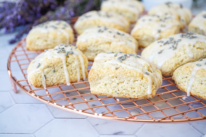 Lavender Vanilla Scones on a copper round wire rack with lavender in the background.