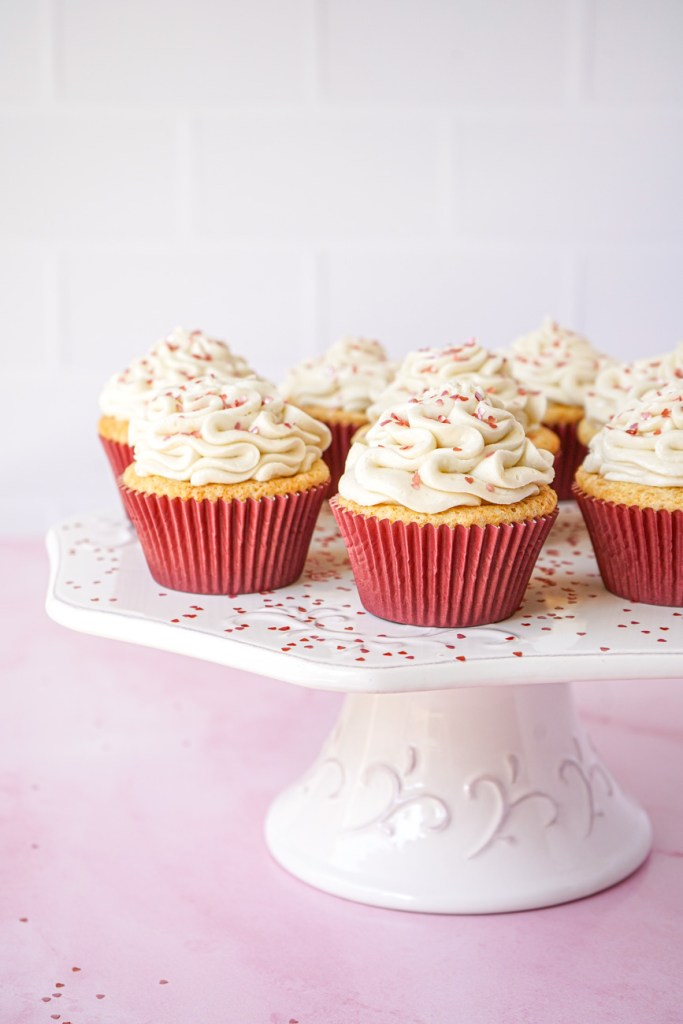 White Chocolate Cupcakes on a white platter with heart glitter.