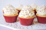 White chocolate cupcakes in maroon liners with heart glitter.