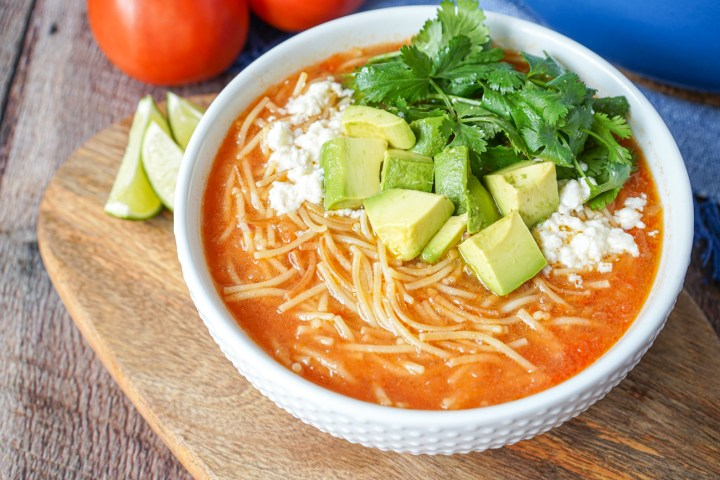 Close up of Sopa de Fideo (Mexican Noodle Soup) in a white bowl with cilantro, cheese, and avocado.