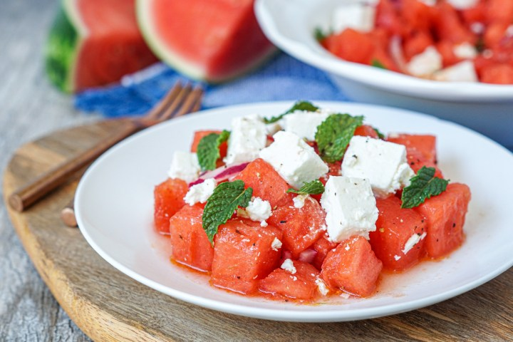 Karpouzi me Feta (Greek Watermelon with Feta) on a white plate over a wooden board with more in the background in a serving bowl.