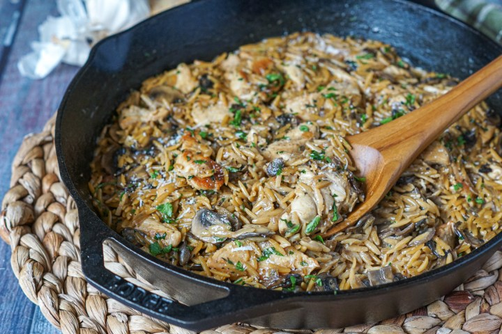 Close up of Chicken and Mushroom Orzo in a cast iron pan with a large wooden spoon.