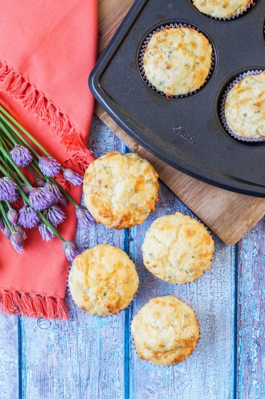 Aerial view of Cheddar Chive Muffins next to purple chive blossoms and a coral-colored napkin.