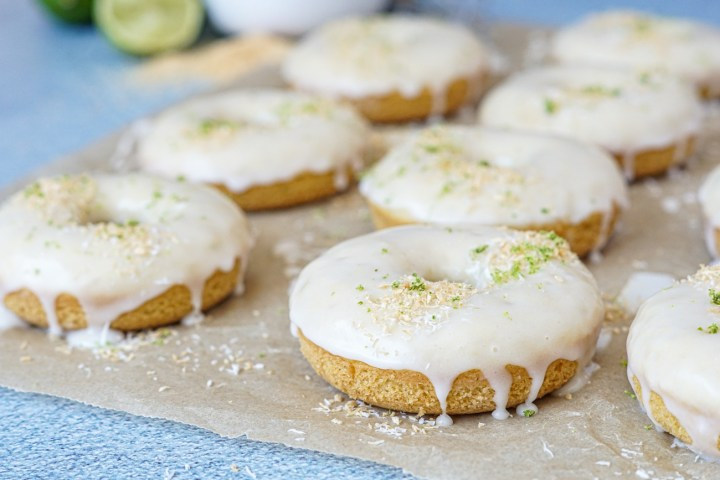 Coconut Lime Baked Donuts on a sheet of parchment paper with lime halves and toasted coconut in the background.