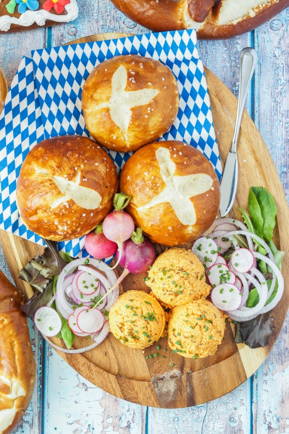 Aerial view of three scoops of Obatzda (Bavarian Cheese and Beer Spread) on a wooden platter with blue and white napkins, three pretzel rolls, radishes, and red onion.