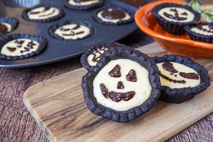 Cheesecake Tartlets with Chocolate Ganache pumpkin faces on a wooden board and in a pan.