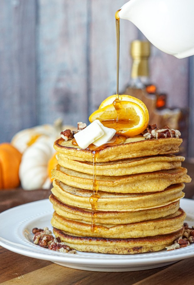 Drizzling maple syrup over a stack of seven Orange Pumpkin Pancakes.
